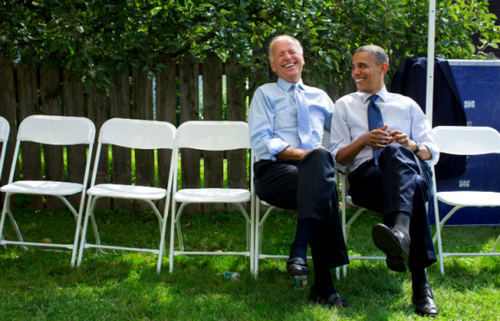 In New Hampshire, Sept. 7, 2012. President Obama sits on a white folding chair next to Vice President Biden joking with the Vice President Joe Biden before a campaign rally in Portsmouth. The two look at each other smiling.