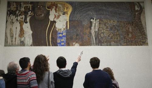 Visitors look at Gustav Klimt's Beethoven Frieze, one of the country's most famous artworks, at the Secession museum in Vienna March 5, 2015. Austria is ready to return the artwork to heirs of its former owners if a review supports their claim they were forced to sell it at a knock-down price. The case, which will test Austria's laws on restitution of looted art, centres on the Lederer family, Jews who fled to Switzerland when Nazi Germany annexed Austria in 1938 and seized the family's extensive art collection. Picture taken March 5, 2015. REUTERS/Leonhard Foeger (AUSTRIA - Tags: POLITICS ENTERTAINMENT CRIME LAW) - GM1EB361AX001