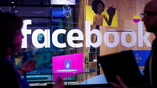 FILE - In this April 18, 2017, file photo, conference workers speak in front of a demo booth at Facebook's annual F8 developer conference, in San Jose, Calif. P Facebook is facing the most serious crisis in its 14-year history as it deals with fallout from a major leak of user data to political consultants associated with the 2016 Trump campaign.